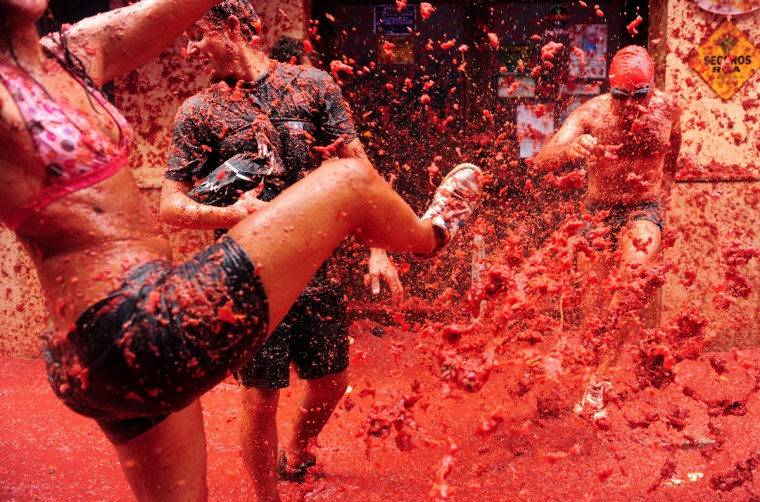 Revellers pelt each other with tomato pulp during the world's biggest tomato fight at La Tomatina festival on August 26, 2009 in Bunol, Spain. More than 45000 people from all over the world descended on the small Valencian town to participate in this year's La Tomatina festival, with the local town hall estimating that over 100 tons of rotten and over-ripe tomatoes were thrown. (Photo by Jasper Juinen/Getty Images)