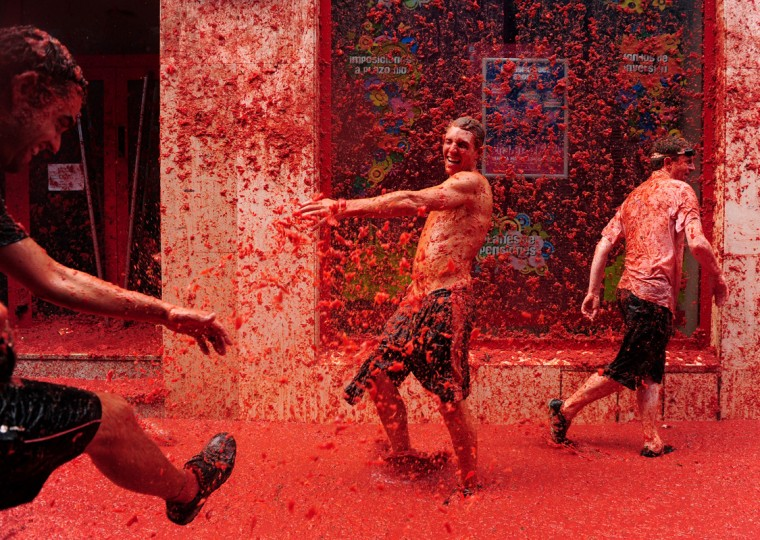 Revellers pelt each other with tomatoe pulp during the world's biggest tomato fight at La Tomatina festival on August 26, 2009 in Bunol, Spain. More than 45000 people from all over the world descended on the small Valencian town to participate in this year's La Tomatina festival, with the local town hall estimating that over 100 tons of rotten and over-ripe tomatoes were thrown. (Photo by Jasper Juinen/Getty Images)