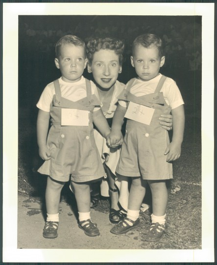 Philip and Howard Hiob were declared most identical twins. Their mother, Mrs. Richard Hiob, 7 Right Wing Drive, Baltimore, peers from between them. (Sun photographer Robert M. Motta/August 21, 1949)