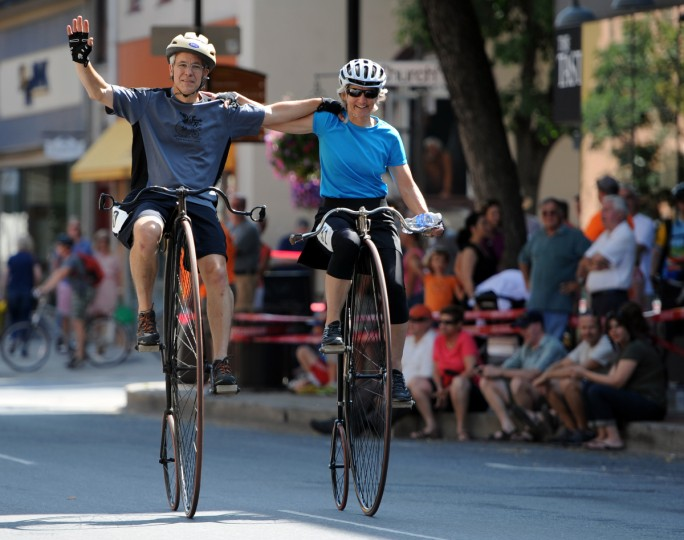 "From left, James and Lori Woodward of Merrimack, N.H., with arms upon each other's shoulders, ride their high wheel bicycles on North Market Street before the start of the 2014 Frederick Clustered Spires High Wheel Race. James is on a 1885 52"" Victor and Lori pedals a 1889 49"" Columbia Light Roadster. This is her first criterium. (Kim Hairston/Baltimore Sun)"