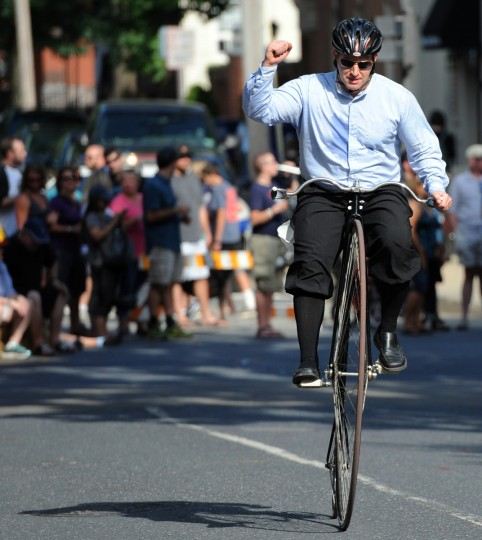 Haig Colter of Bethesda is cheered by the crowd as he pumps his fist during a lap in the 2014 Frederick Clustered Spires High Wheel Race. (Kim Hairston/Baltimore Sun)