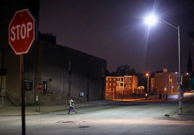 An 11-year-old boy crosses the street in East Baltimore just two minutes before the 9pm Baltimore City curfew for youth. (Al Drago/Baltimore Sun)