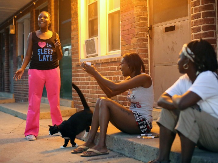 Amyra Carr, 10, sings outside of her home in West Baltimore alongside Nicole Williams, center, her mother, Kelly Carr, right, and their cat Oreo, before the 9pm curfew for youth in Baltimore City. (Al Drago/Baltimore Sun)