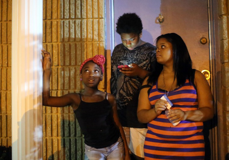Shakiera Thompson, 10, looks to the sky as a police helicopter shines its light through the street as she stands on the porch with Myketa Wills, 19, right, and her brother Jordan Wills, 13, center, before the 9pm curfew for youth in Baltimore City. (Al Drago/Baltimore Sun)