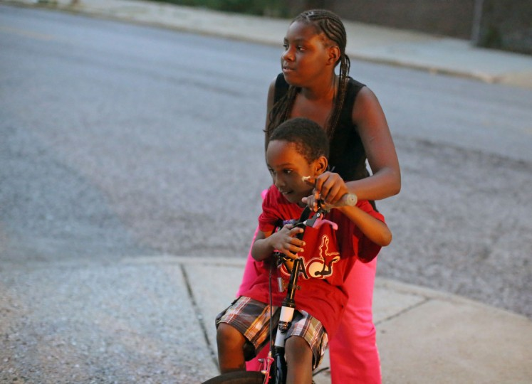 Amyra Carr, 10, turns the biker around with Isaiah Turner, 8, as they circle the block one more time before the 9pm curfew for youth in Baltimore City. (Al Drago/Baltimore Sun)