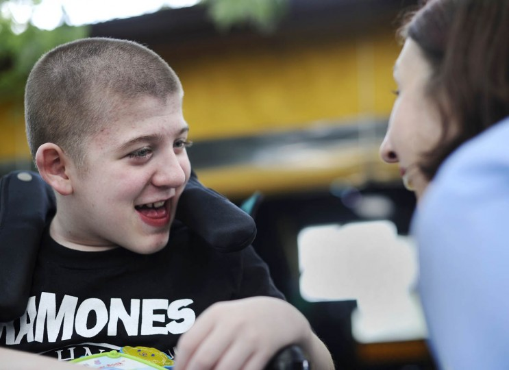Mickey Smith, 12, smiles at his mother, Cathy Smith, both of Gambrills, at a fundraiser for Mickey's genetic testing. Mickey has a progressive neuromuscular disease. (Rachel Woolf/Baltimore Sun)