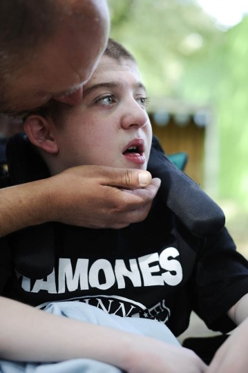 Michael Smith Jr. kisses his son, Mickey Smith's face at a fundraiser for Mickey's genetic testing. Mickey has a progressive neuromuscular disease. (Rachel Woolf/Baltimore Sun)