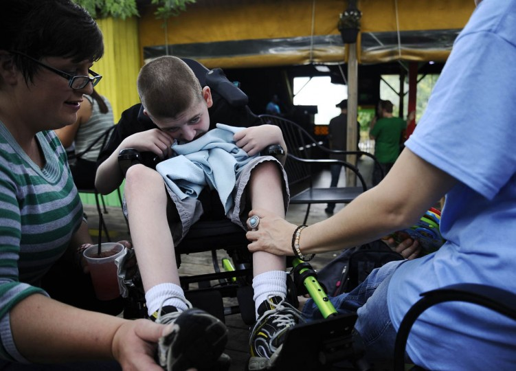 Charlene Mamula, of Fairfield, PA, Cathy's cousin, on left, adjusts Mickey Smith's shoes while Mickey's mother, Cathy Smith, looks on during a fundraiser for Mickey's genetic testing. Mickey has a progressive neuromuscular disease. (Rachel Woolf/Baltimore Sun)