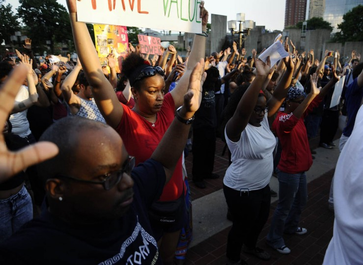 Beth Gillus, of Baltimore, center, raises her hands and her sign along with the rest of the crowd during a moment of silence at the inner harbor during the solidarity rally and march Thursday evening for Michael Brown of Ferguson, Missouri. (Rachel Woolf/Baltimore Sun)