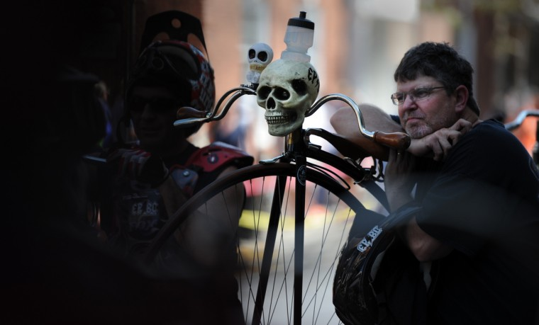 Brian Weber of Gerrardstown, W.Va., leans on the frame of his Josef Mesicek penny farthing bicycle as he listens to instructions before riders line up for the 2014 Frederick Clustered Spires High Wheel Race. (Kim Hairston/Baltimore Sun)