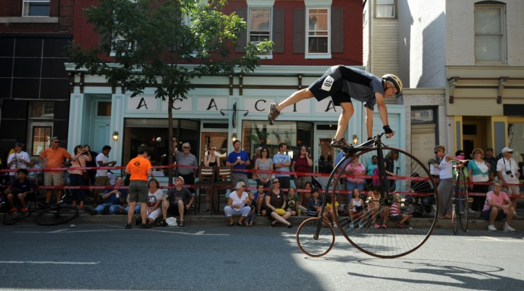 """James Woodward of Merrimack, N.H., shows it is possible to ride a high wheel bicycle from an even more elevated position. Woodward shows his skill, balancing on his 1885 52"""" Victor penny farthing, on North Market Street before the start of the race. (Kim Hairston/Baltimore Sun)"""
