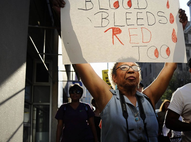 "Kay Adler, of Baltimore, holds up a sign reading ""black blood bleeds red too"" Thursday evening at the solidarity rally and march for Michael Brown of Ferguson, Missouri. (Rachel Woolf/Baltimore Sun)"