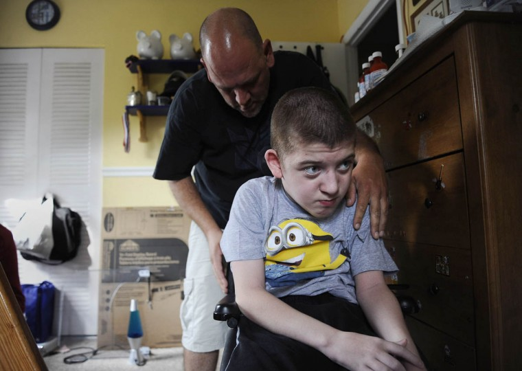 "Michael Smith Jr., prepares to wheel his son Mick Smith, 12, both of Gambrills, out of his room for ""toy time."" Mick has an undiagnosed neuromuscular disease. (Rachel Woolf/Baltimore Sun)"
