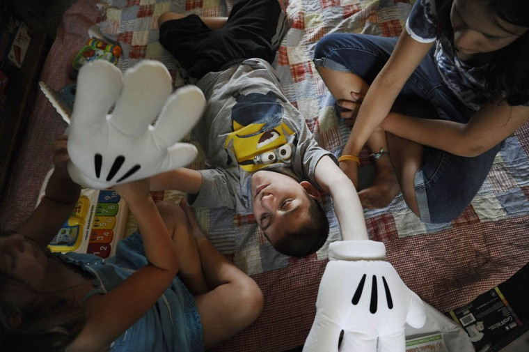 Martie Smith, 7, on left, puts large gloves on her brother, Mick Smith, 12, while their sister Grace Smith, 12, holds Mick's arm. Mick has an undiagnosed neuromuscular disease. (Rachel Woolf/Baltimore Sun)