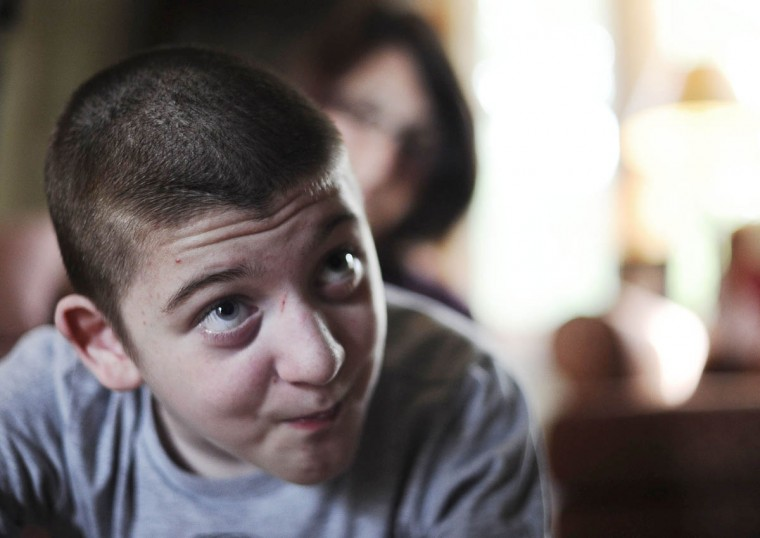 Mick Smith, 12, looks up while his mom Cathy Smith looks on behind him. Mick has an undiagnosed neuromuscular disease. (Rachel Woolf/Baltimore Sun)