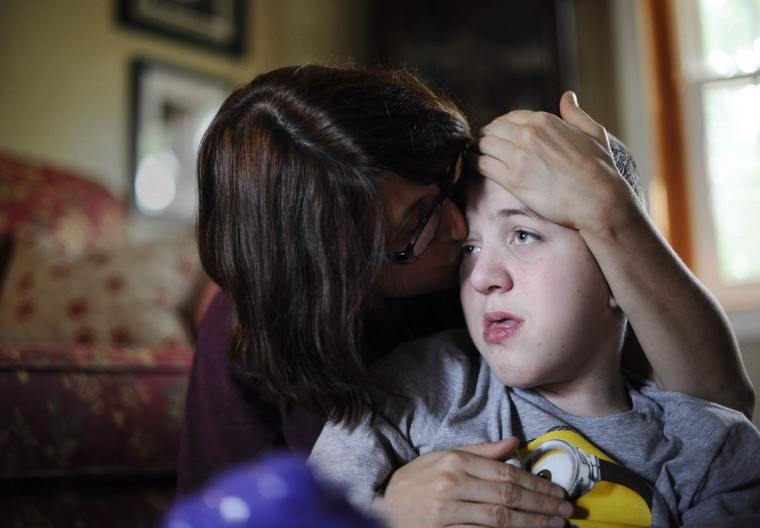 Cathy Smith, kisses her son, Mick Smith's cheek. Mick has an undiagnosed neuromuscular disease. (Rachel Woolf/Baltimore Sun)