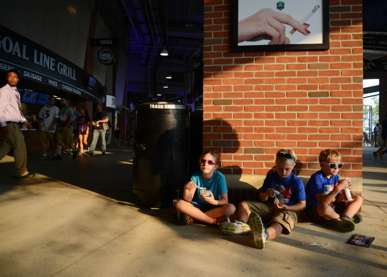 From left, Sara Jurkovic, 10, John Jurkovic, 7 and Nate Jurkovic, 7, all of Baltimore, eat snacks before the Ravens game against the San Francisco 49ers at M&T Bank Stadium on August 7, 2014. (Rachel Woolf/Baltimore Sun)