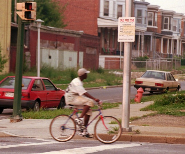 A bicycle rider rides past a Drug Free Zone sign posted on a light pole at the corner of Woodland and Park Heights Avenues. The intersection is a known and active drug corner and is a hangout for area drug dealers. (Photo: Garo Lachinian/Baltimore Sun/August 1963)