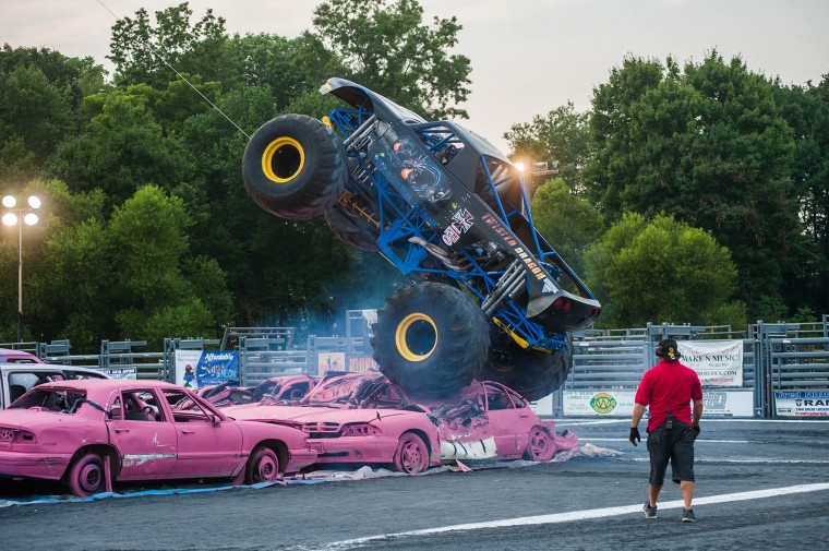 A monster truck leaps a row of pink cars during the monster truck races at the Howard County Fair on Wednesday, August 6. (Noah Scialom/BSMG)