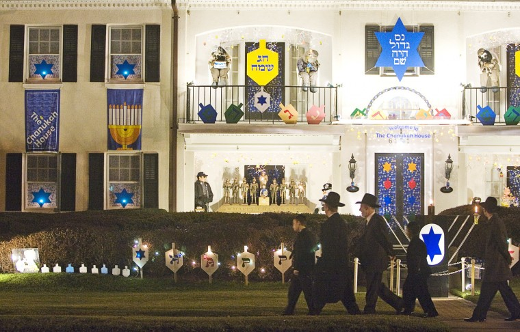 "Orthodox Jews walk past the Chanukah House on Park Heights Avenue on their way to synagogue on Dec. 15, 2006. Every year, the owners of the house make their home into a Chanukah attraction with traditional symbols and fun modern displays like ""Herschel Harry Potter and his Golden Dreidel Snitch."" (Sarah Nix /Baltimore Sun)"