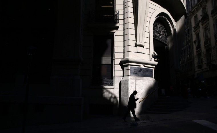"A man is silhouetted as he looks at his phone while walking in Buenos Aires' financial district, August 14, 2014. The hedge funds suing Argentina over its 2002 debt default are an ""international mafia"" out to wreck the country's finances, the government said on Thursday, pumping up the rhetoric in a battle that is squeezing the struggling Argentine economy. (Marcos Brindicci /Reuters)"