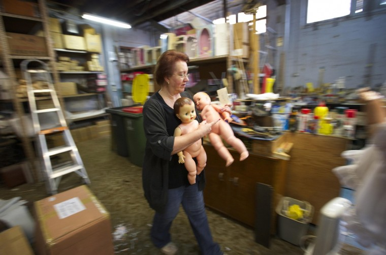 Australian doll repairer Kerry Stuart, a 25-year veteran at Sydney's Doll Hospital, carries spare dolls to be used for parts in repairing customer's dolls. (Jason Reed/Reuters)