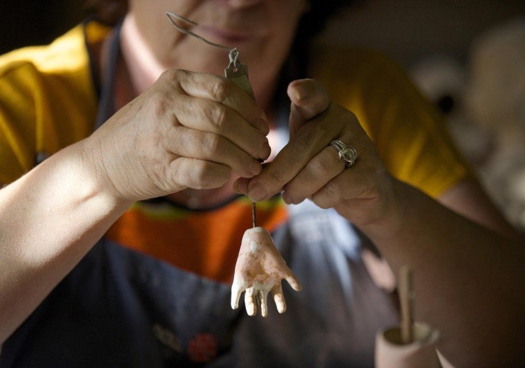 Gail Grainger, a 14-year veteran doll restorer, is pictured as she adds fingers to a damaged dolls hand in her workshop at Sydney's Doll Hospital. (Jason Reed/Reuters)