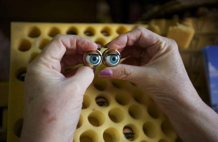 Australian doll repairer Kerry Stuart, a 25-year veteran at Sydney's Doll Hospital, matches a pair of eyes from her stock to be inserted into a customer's doll undergoing repairs. (Jason Reed/Reuters)