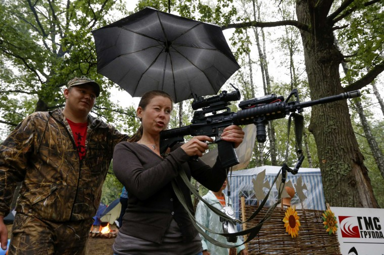 A member from the Belarussian pro-government youth organisation takes aim at balloons with an air gun during their annual meeting in a forest, near the village of Dumanovshchina, southeast of Minsk, August 16, 2014. Through this camp, the group aims to promote patriotism and instil moral values into youth. REUTERS/Vasily Fedosenko
