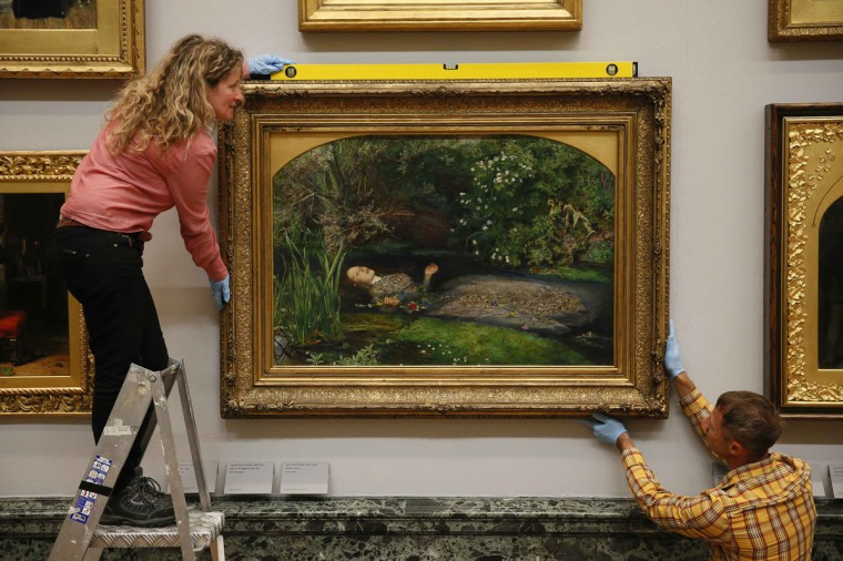 "Tate staff pose with the painting ""Ophelia"" by John Everett Millais at the Tate Modern in London August 7, 2014. The painting returns home to Tate Britain following an international tour. (Stefan Wermuth/Reuters)"