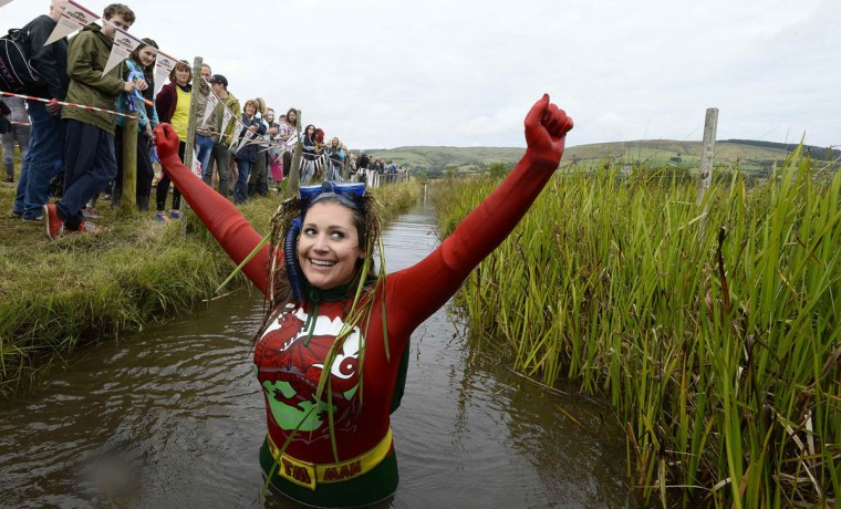 Joanna Parker celebrates finishing in the World Bog Snorkeling Championships at Waen Rhydd bog on the outskirts of LLanwrtyd Wells, Powys, Wales August 24, 2014. The annual event, where competitors swim in a marshy trench with flippers and a snorkel, brings together participants from all over the world, including France, Germany, Australia, New Zealand, the U.S. and Canada. (Rebecca Naden/Reuters)