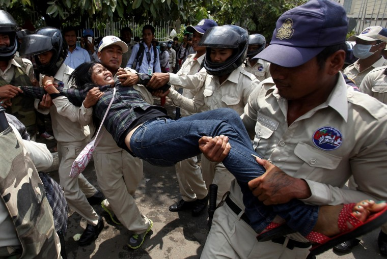 Cambodian security officers carry a woman during a protest near the National Assembly in Phnom Penh. Boeung Kak lake residents and other communities who are embroiled in land disputes gathered near the National Assembly to appeal for help from the government. (Samrang Pring/Reuters)