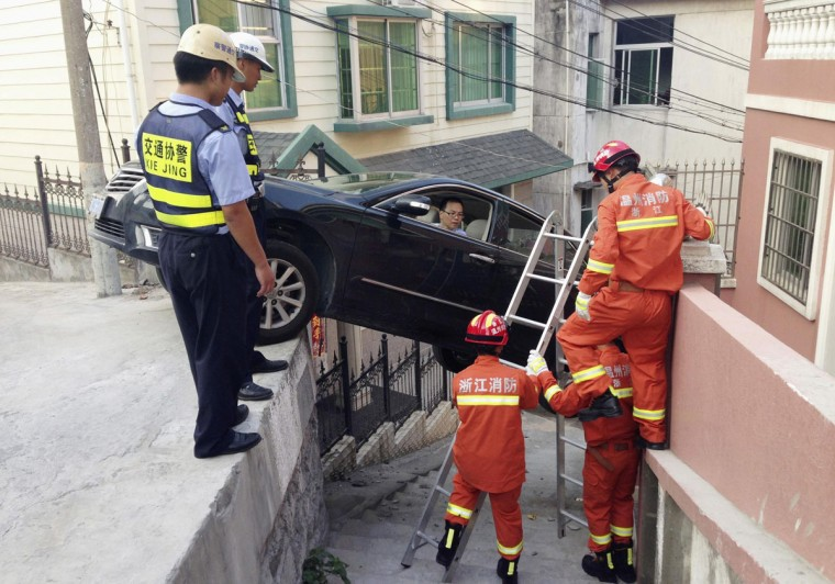 Rescue workers try to help a driver out of his car, after the vehicle was stuck over an alley in Wenzhou, Zhejiang province, August 4, 2014. The car rolled off the edge of a road after the driver was late to brake, according to local media. Picture taken August 4, 2014. (REUTERS/Stringer)