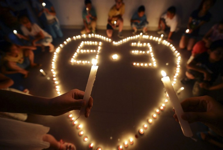 Children hold candles as they pray for those affected after a magnitude 6.3 earthquake hit Longtoushan town, Ludian county of Zhaotong, Yunnan province, in Yangzhou, Jiangsu province, August 4, 2014. The death toll from the earthquake that hit southwestern China on Sunday climbed to 398 people, state media reported on Monday. The numbers 8 and 3 in the centre of the heart refer to August 3, the date the earthquake occurred. Picture taken August 4, 2014. (REUTERS/Stringer)