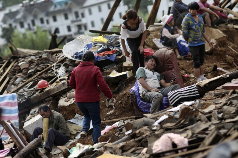 Liu Jiali (C) sits on a sofa next to his collapsed house as rescuers are trying to find his wife and child who were buried underneath the debris after an earthquake hit Longtoushan township of Ludian county, Yunnan province August 4, 2014. A magnitude 6.3 earthquake struck southwestern China on Sunday, killing at least 398 people in a remote area of Yunnan province, and causing thousands of buildings, including a school, to collapse. (REUTERS/Wong Campion)