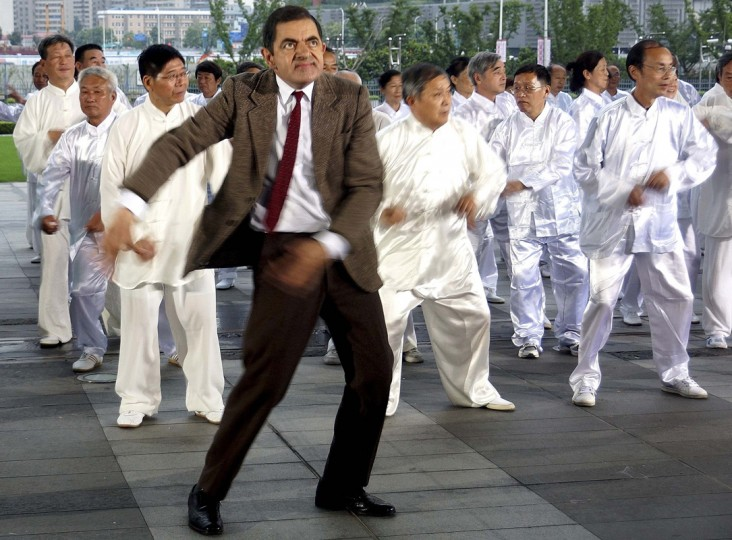 British actor Rowan Atkinson (front), dressed in his popular television character Mr. Bean, dances with Chinese performers during the filming of a promotional video in Shanghai August 20, 2014. Picture taken August 20, 2014. (Stringer/Reuters)