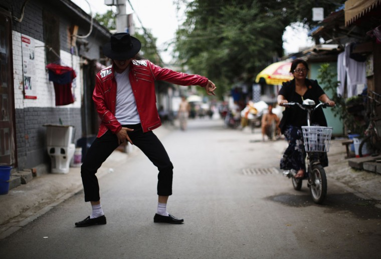 Zhang Guanhui, impersonating Michael Jackson, dances in front of his house located in a village for migrant workers during an interview with Reuters in Beijing July 22, 2014. Zhang, born in 1984, quit elementary school and has since held jobs as a factory worker, waiter, and security guard. After watching a Michael Jackson music video four years ago for the first time, Zhang says he became fascinated and now puts on shows on the street and small stages impersonating the King of Pop. Picture taken July 22, 2014. (Kim Kyung-Hoon/Reuters)
