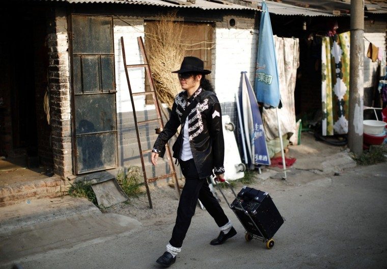 Zhang Guanhui, impersonating Michael Jackson, walks with an amplifier in a village for migrant workers, on his way downtown for his street performance in Beijing August 20, 2014. Zhang, born in 1984, quit elementary school and has since held jobs as a factory worker, waiter, and security guard. After watching a Michael Jackson music video four years ago for the first time, Zhang says he became fascinated and now puts on shows on the street and small stages impersonating the King of Pop. (Kim Kyung-Hoon/Reuters)