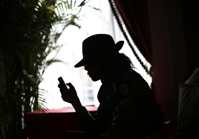 Zhang Guanhui, imitating Michael Jackson, is silhouetted as he uses his mobile phone while waiting to perform, in a dressing room in Langfang, Hebei province July 19, 2014. Zhang, born in 1984, quit elementary school and has since held jobs as a factory worker, waiter, and security guard. After watching a Michael Jackson music video four years ago for the first time, Zhang says he became fascinated and now puts on shows on the street and small stages impersonating the King of Pop. (Kim Kyung-Hoon/Reuters)