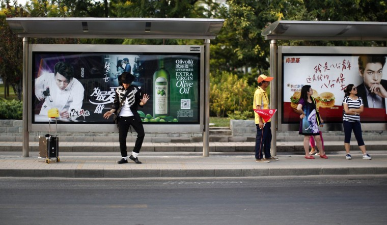 Zhang Guanhui, impersonating Michael Jackson, practices his dance moves at a bus stop as he waits for a bus heading downtown for his street performance in Beijing August 20, 2014. Zhang, born in 1984, quit elementary school and has since held jobs as a factory worker, waiter, and security guard. After watching a Michael Jackson music video four years ago for the first time, Zhang says he became fascinated and now puts on shows on the street and small stages impersonating the King of Pop. Picture taken August 20, 2014. (Kim Kyung-Hoon/Reuters)
