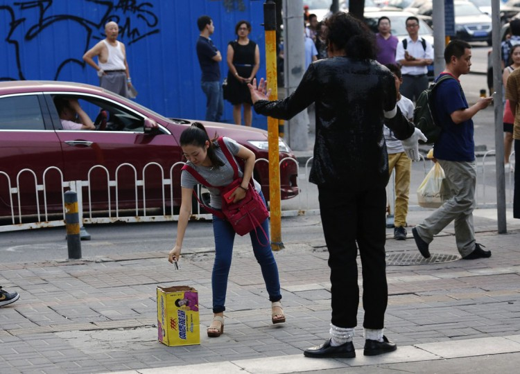 A bystander puts a money into a box after watching a street performance by Zhang Guanhui, impersonating Michael Jackson, in Beijing August 20, 2014. Zhang, born in 1984, quit elementary school and has since held jobs as a factory worker, waiter, and security guard. After watching a Michael Jackson music video four years ago for the first time, Zhang says he became fascinated and now puts on shows on the street and small stages impersonating the King of Pop. Picture taken August 20, 2014. (Kim Kyung-Hoon/Reuters)