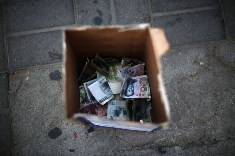 Money from bystanders is seen in a box after a street performance by Zhang Guanhui, impersonating Michael Jackson, in Beijing August 20, 2014. Zhang, born in 1984, quit elementary school and has since held jobs as a factory worker, waiter, and security guard. After watching a Michael Jackson music video four years ago for the first time, Zhang says he became fascinated and now puts on shows on the street and small stages impersonating the King of Pop. (Kim Kyung-Hoon/Reuters)