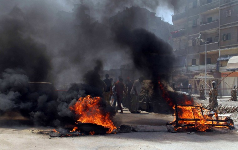 Protesters, supporters of the Muslim Brotherhood, are seen behind burning tires during a protest in the Matariya area in Cairo, August 14, 2014. Security was tightened on Thursday, which was the one-year anniversary of the clearing of the Muslim Brotherhood sit-in at Cairo's Rabaa al-Adawiya, where at least 817 protesters were killed when security forces stormed two protest. (Al Youm Al Saabi Newspaper/Reuters)