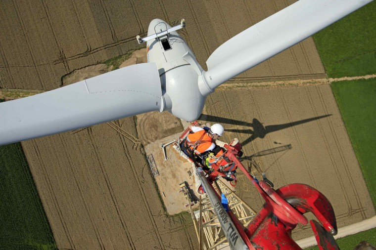 Employees work on a crane above an E-70 wind turbine manufactured by German company Enercon for La Compagnie du Vent (GDF SUEZ Group) during its installation at a wind farm in Meneslies, Picardie region, July 31, 2014. France announced in July a package of tax breaks and low-cost loans to improve insulation in buildings and boost investment in renewable energy, which is supposed to provide 40 percent of the country's electricity by 2030. Picture taken July 31, 2014. (REUTERS/Benoit Tessier)
