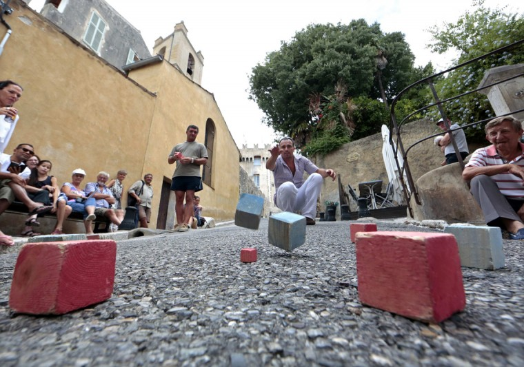 A competitor strikes a boule as he attends the square boules world championship in Cagnes, August 16, 2014. 330 competitors of different countries compete in this unique two days championship. REUTERS/Eric Gaillard