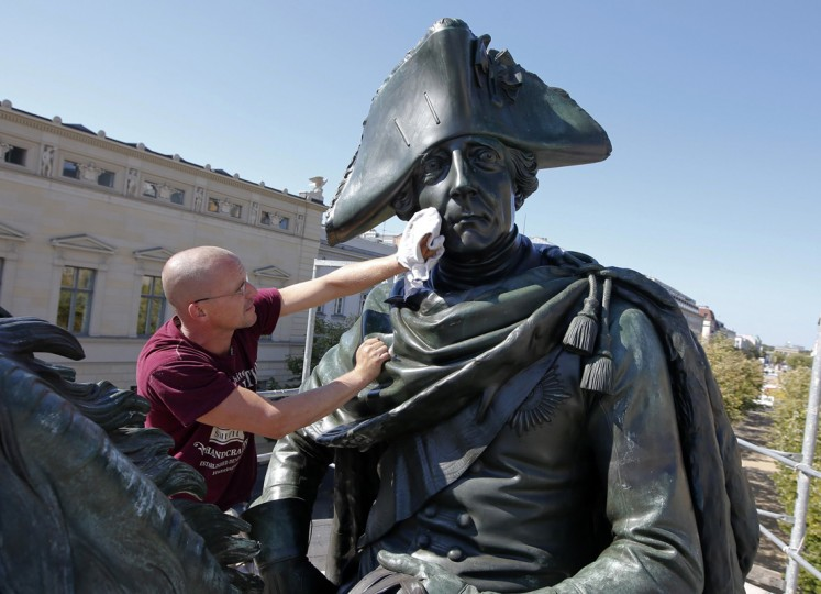 Marco Paul of Seiler foundry varnishes the surface of a bronze statue of Prussian king Frederick the Great at Unter den Linden street in Berlin August 28, 2014. At regular intervals the equestrian monument to honor Frederick II. of Prussia, created by German sculptor Christian Daniel Rauch is varnished with a special wax polish to protect it against environmental influences. (Fabrizio Bensch/Reuters)