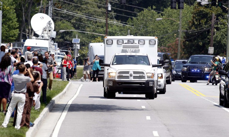 An ambulance carrying American missionary Nancy Writebol, 59, who is infected with Ebola in West Africa arrives past crowds of people taking pictures at Emory University Hospital in Atlanta, Georgia August 5, 2014. Writebol arrived in the United States after being flown overnight from Liberia and will be treated by infectious disease specialists at Emory University Hospital, according to Christian missionary group SIM USA. She will be in the same isolation ward as Kent Brantly, 33, an Ebola-infected American doctor who was able to walk into the hospital when he arrived by ambulance on Saturday. The pair are believed to be the first Ebola patients ever treated in the United States, and health officials have said the virus does not pose a significant threat to the public. (REUTERS/Tami Chappell)