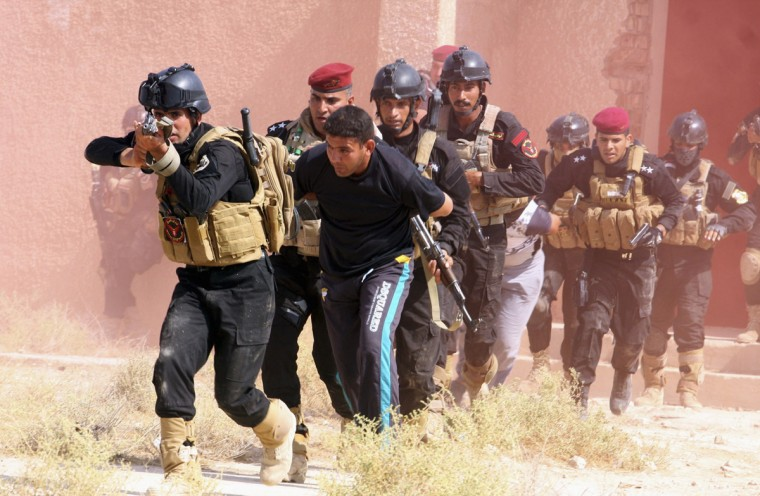 Iraqi Special police officers demonstrate their skills during a graduation ceremony in Kerbala, southwest of Baghdad, August 21, 2014. (Mushtaq Muhammed/Reuters)