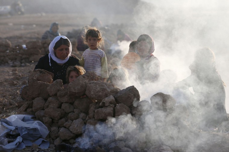 Displaced people from the minority Yazidi sect, who fled violence in the Iraqi town of Sinjar, are seen as they prepare tea for breakfast at Bajed Kadal refugee camp, southwest of Dohuk province, August 23, 2014. (Youssef Boudlal/Reuters)