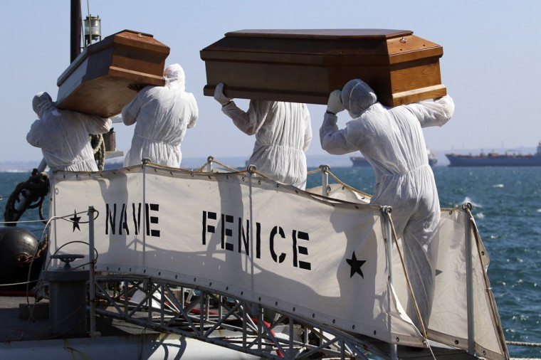 Coffins containing bodies of migrants who died are carried off a navy ship at the Sicilian harbour of Augusta August 26, 2014. At least 24 migrants trying to reach Europe from Africa died after their boat sank in the Mediterranean, the Italian navy said on Tuesday after completing a two day search for bodies. A further 364 migrants were rescued by navy and coastguard vessels after the fishing boat capsized on Sunday evening, the latest in a series of similar shipwrecks. (Antonio Parrinello/Retuers)